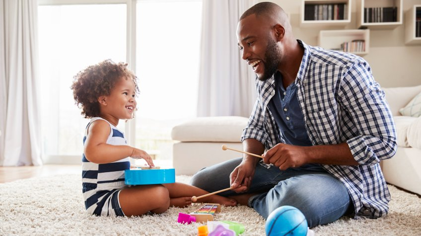 Young black father playing with daughter in the sitting room.