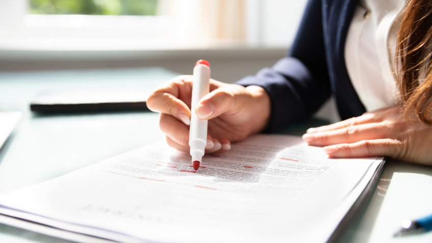 Businesswoman's Hand Marking Error In Contract Form With Marker.