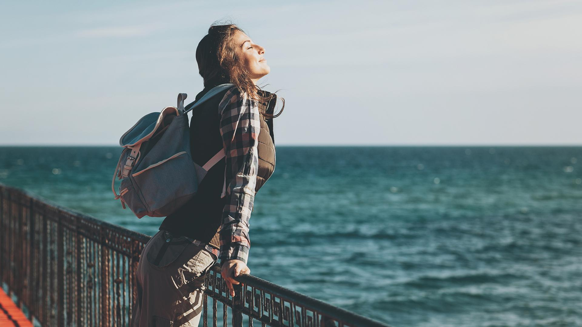Young woman with eyes closed enjoying the air and sea on a sunny day.