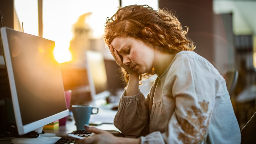 Exhausted redhead programmer holding her head in pain while working in the office.