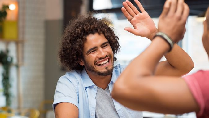 friends giving high five at cafe while having lunch.