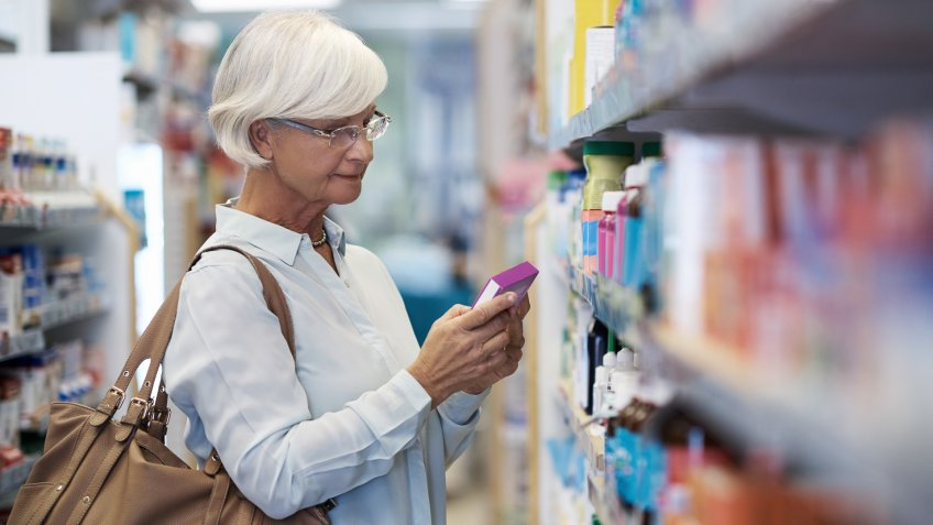 Shot of an elderly woman looking at products in a pharmacy.