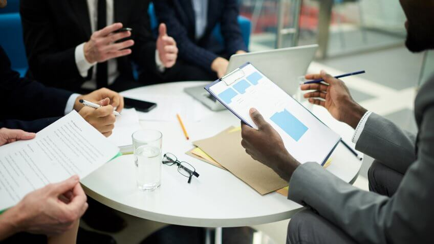 Mid section crop of unrecognizable business people meeting in office, focus on African man holding clipboard, copy space.