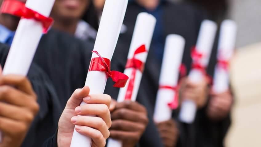 group of multiracial graduates holding diploma.