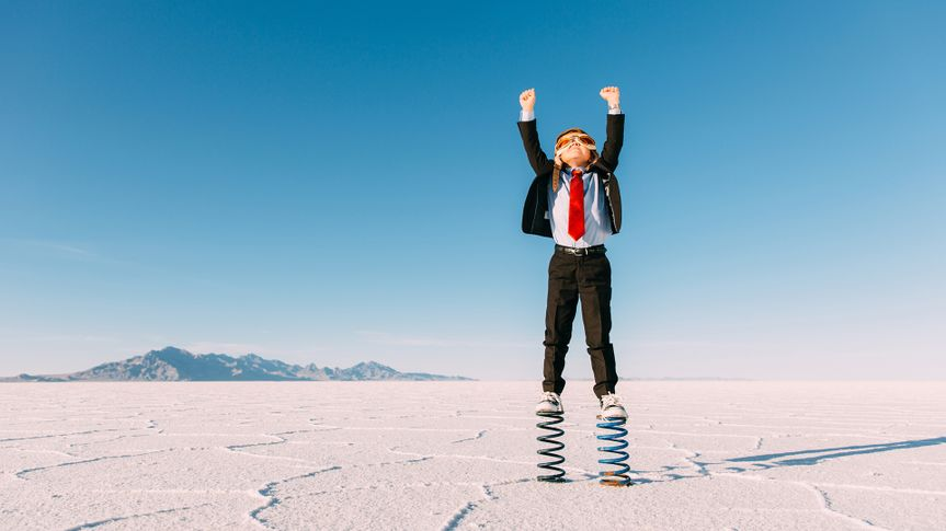 A young business boy dressed in business suit, flight cap and goggles stands on springs in the Utah desert.