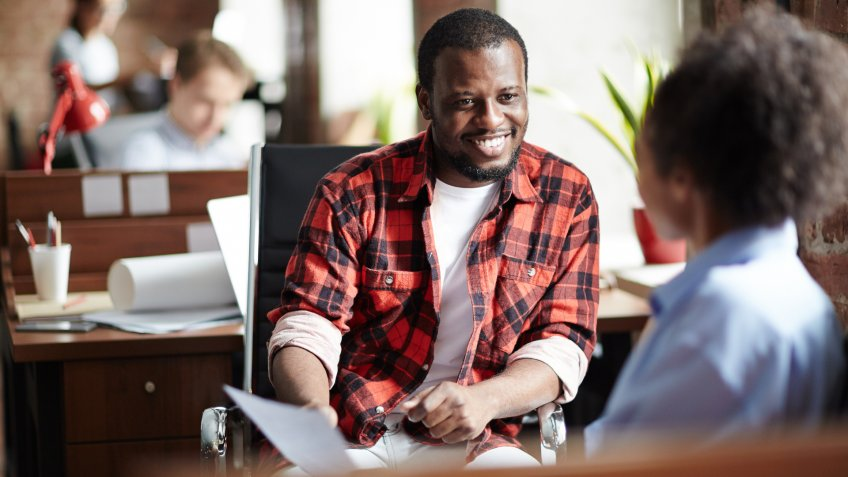 Smiling African businessman in casual clothes conducting the interview with woman at office.