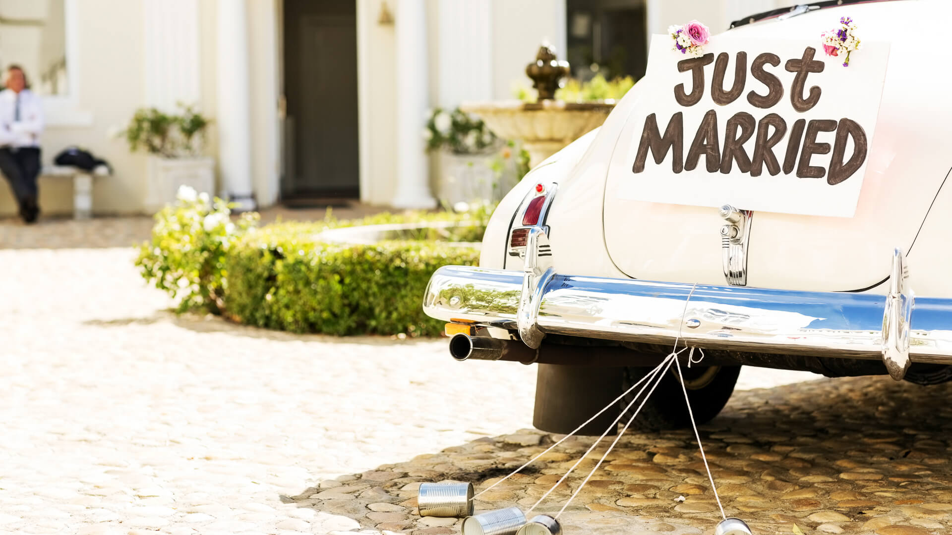 Just married sign and cans attached to convertible car.