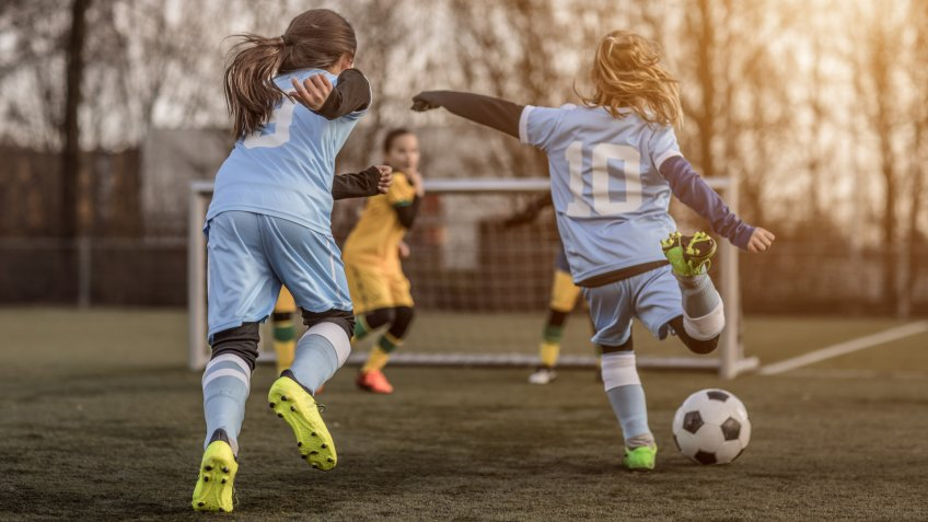Two Female Girl Soccer Teams playing a football training match in the Spring outdoors.