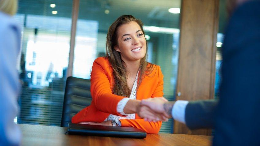 a young graduate sits across the table from her interview panel  full of confidence and positivity energy .
