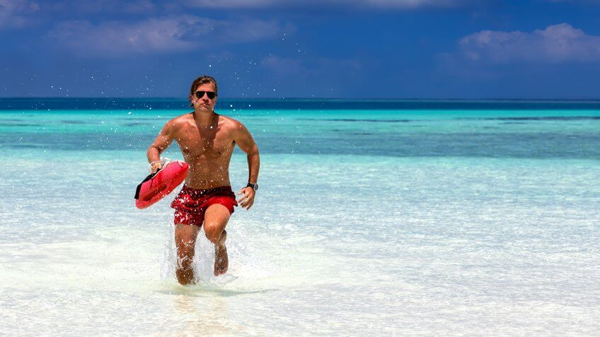 Male lifeguard running in turquoise waters in the Maldives.