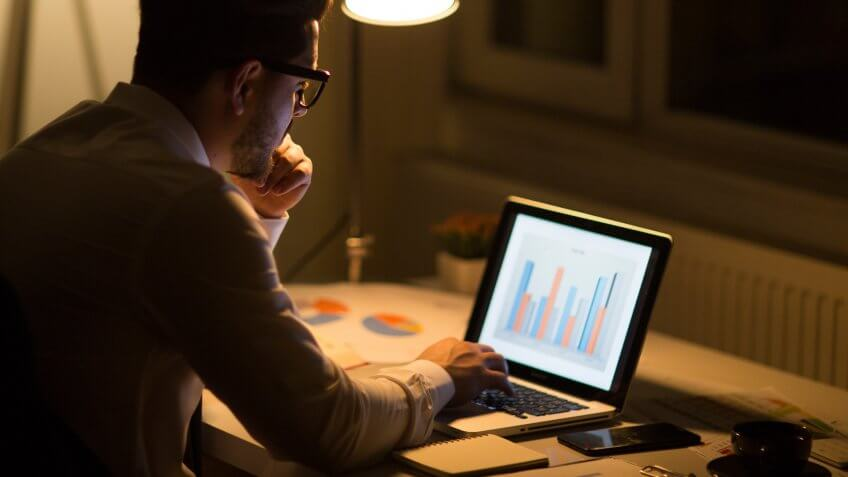 Man working with laptop late at night at home.