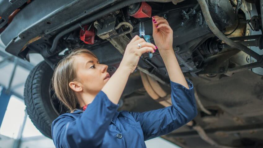 Photo of young female mechanic inspecting a CV join on a car in auto repair shop.