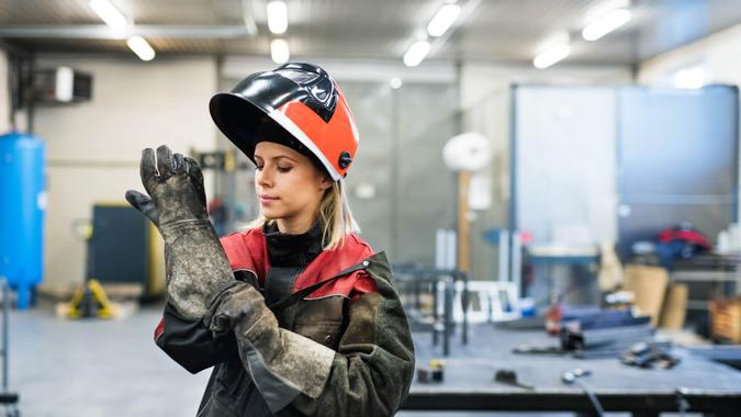 Industrial young woman worker at the welding factory, putting on protective gloves.