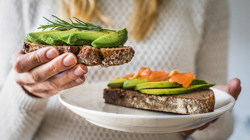 millennial woman eating avocado toast saving her money