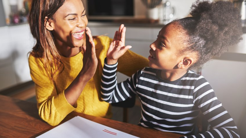 Learning to calculate, high five success, black mother and child.