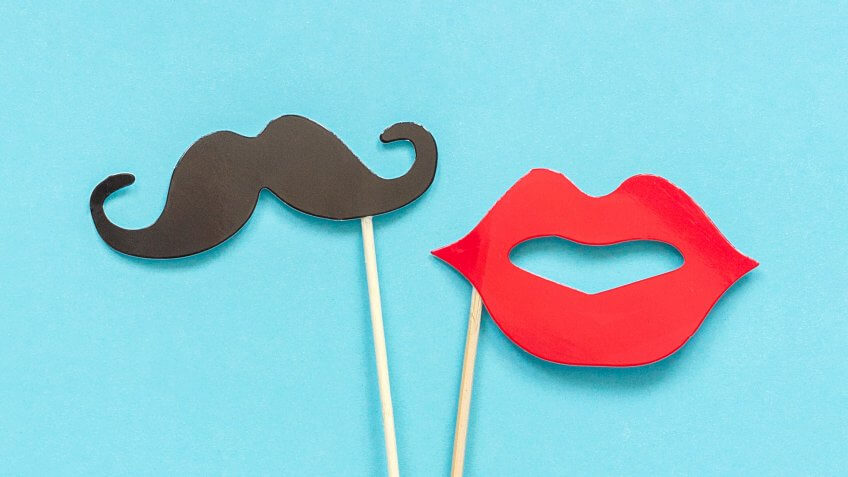 Couple paper mustache and lips props on stick in ice cream waffle cone on blue background.
