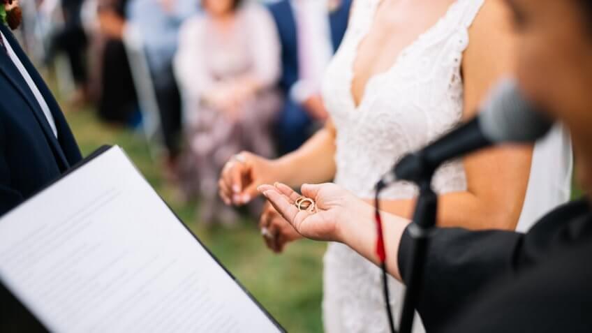 officiant handing wedding rings in hand