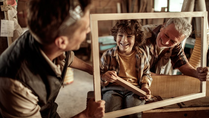 Close up of a boy learning how carpenting works from his father and grandfather.