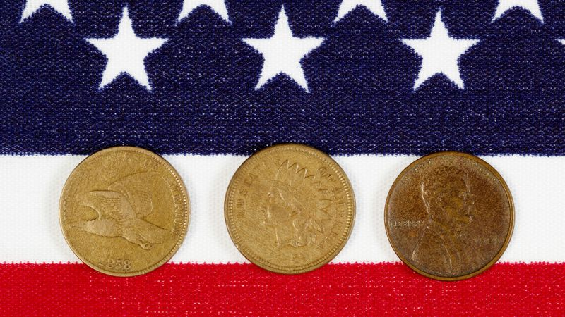 Closeup view of United States One Cent Pieces, original start dates, placed on American Flag.
