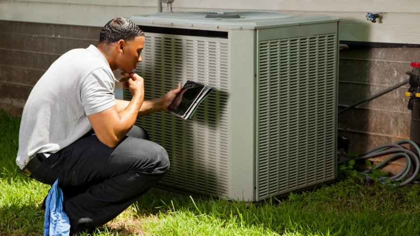 Home inspector, repairman, adjuster examines air conditioner units at a customer's home.