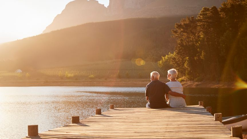Romantic Senior Couple Sitting On Wooden Jetty By Lake.