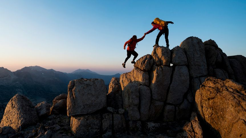 One climber helping the other get to the top of a mountain .