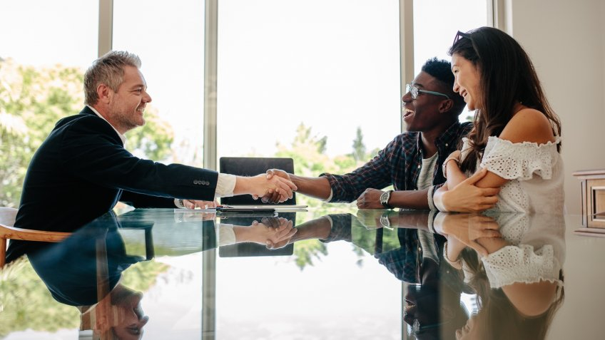 Male real estate broker shaking hands with new property owners while sitting across a table.