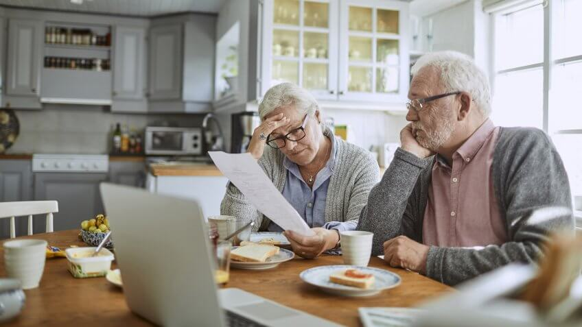 Close up of a senior couple having breakfast and doing bills.