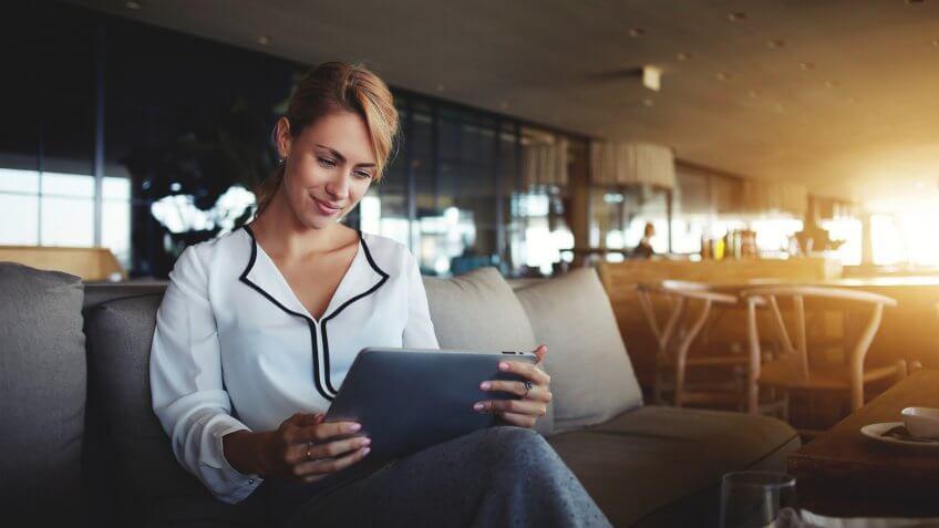 Female financier is reading financial news in internet via touch pad during work break in modern cafe.