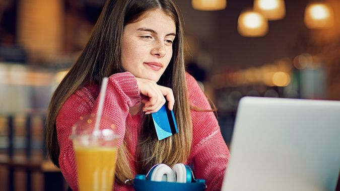 Teenage girl is shopping online with her credit card in a cafeteria.