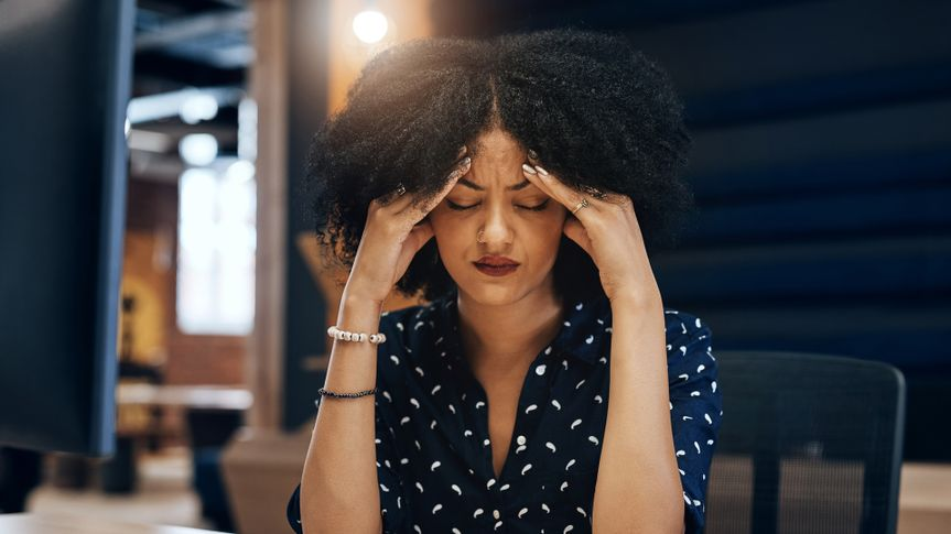 Shot of a tired young female designer looking stressed with her hands in her hair while contemplating in the office at work.