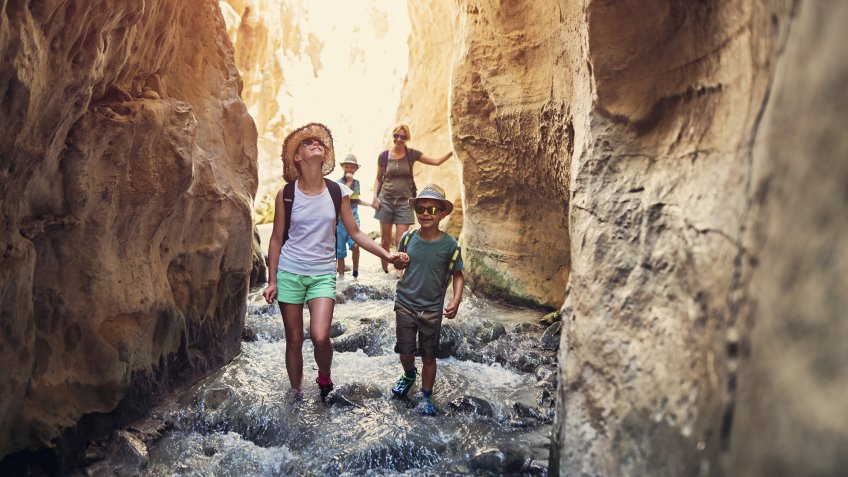 Mother and kids hiking through river Rio Chillar in Andalusia, Spain.