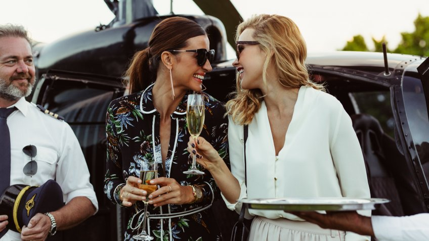 two successful women enjoying champagne after a helicopter ride