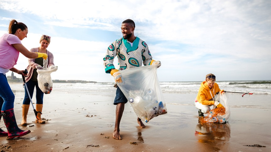 Collecting rubbish off a beach.