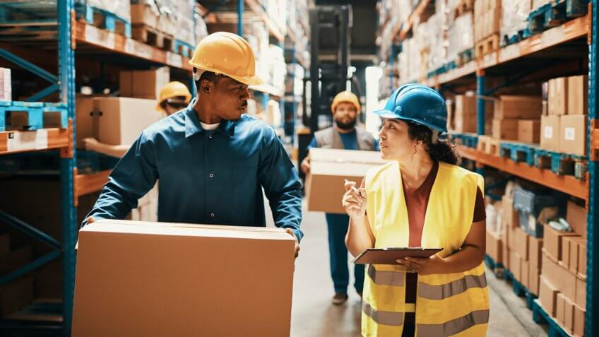 Close up of a group of workers working in a warehouse.