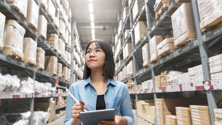 Candid of young attractive asian woman auditor or trainee staff work looking up stocktaking inventory in warehouse store by computer tablet with wide angle view.