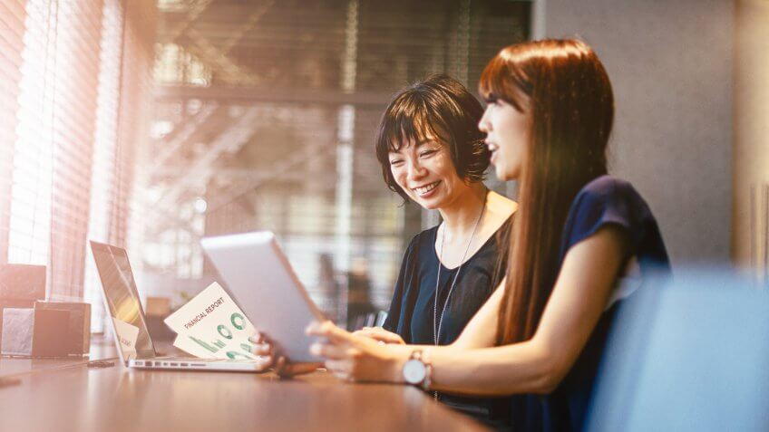 Two young Japanese businesswomen discuss options for investment and other development projects in modern office.