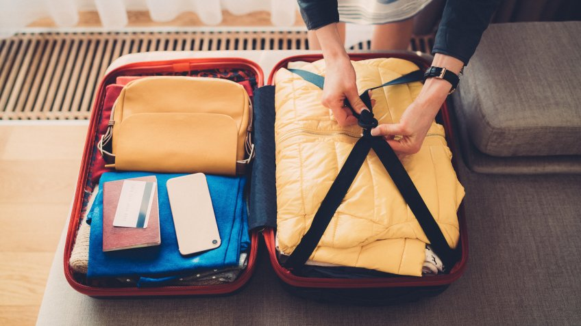 woman preparing her carry on travel bag essentials