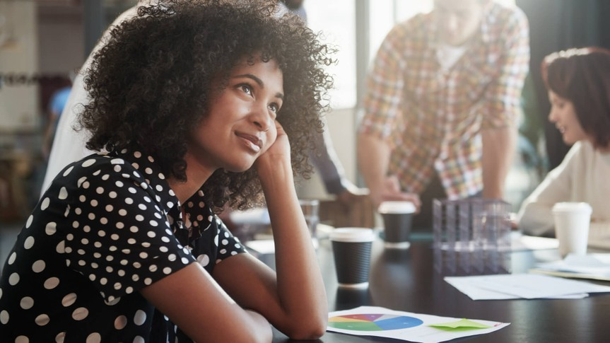 Shot of a young female designer looking thoughtful while sitting at a conference table with her colleagues.