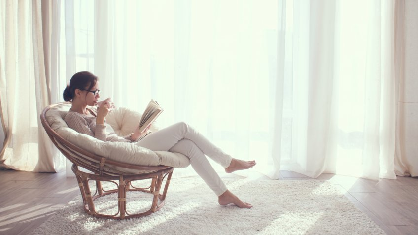 Young woman at home sitting on modern chair in front of window relaxing in her living room reading book and drinking coffee or tea - Image.