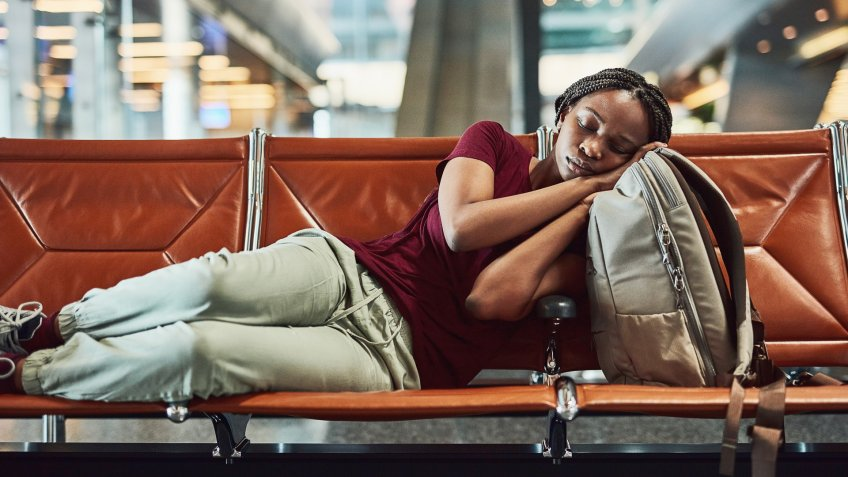 Shot of a young woman falling asleep at the airport while waiting for departure.