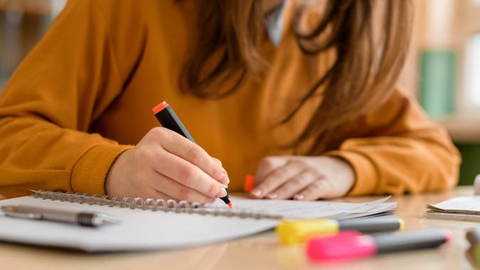 Young unrecognisable female college student in class, taking notes and using highlighter.