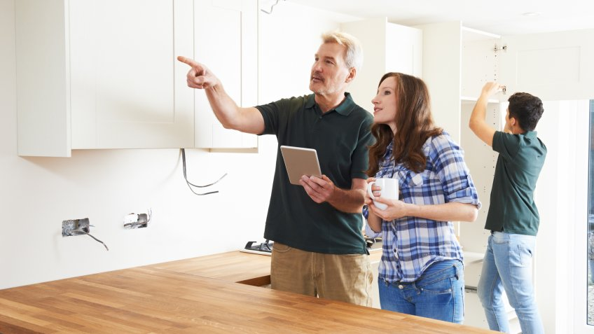 Woman With Carpenter Looking At Plans For Kitchen On Digital Tablet.