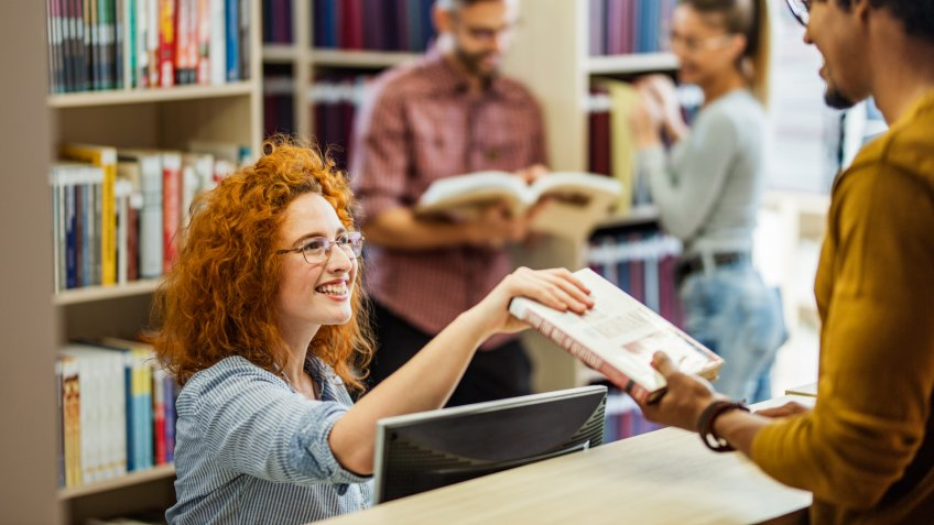 Happy female librarian taking a book from a male student in the library.