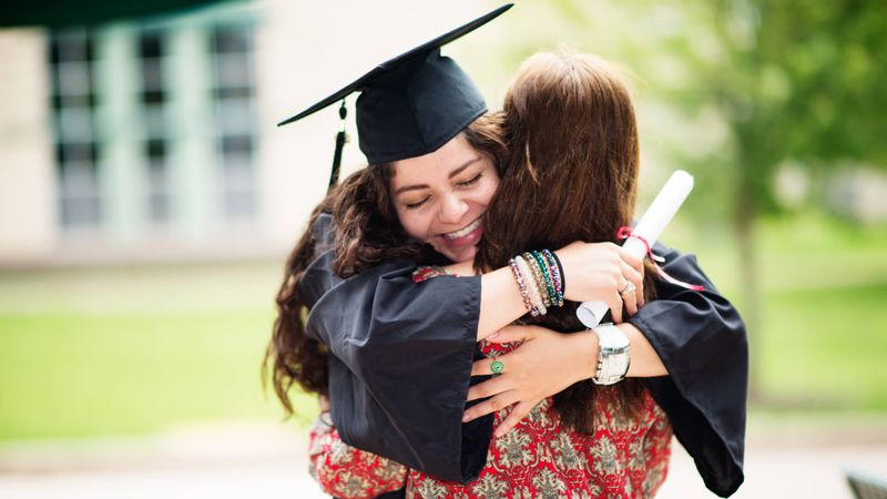 Female college student hugging her mother on graduation date.