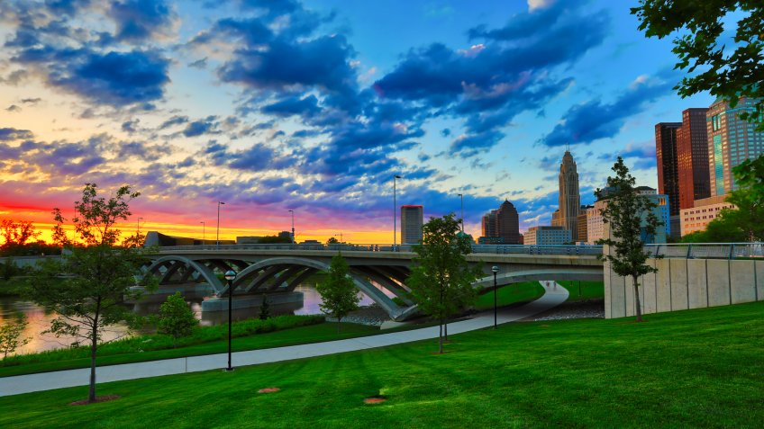 A beautiful sunset in Columbus, Ohio with the Scioto Greenway and the Rich Street Bridge in the foreground.
