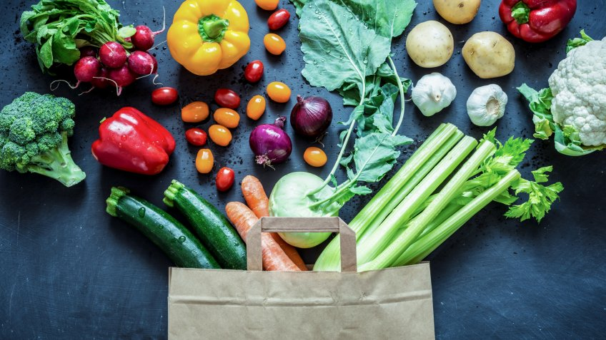 Fresh colorful organic vegetables coming out from paper eco shopping bag