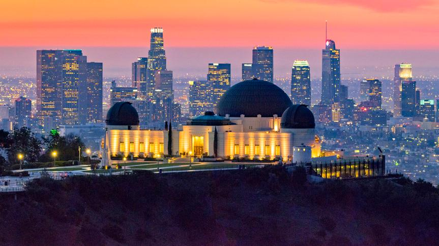 Los Angeles skyline at dawn with Griffith Park Observatory in the foreground.