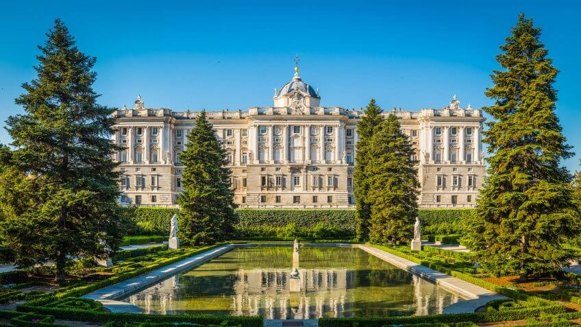 The historic facade of the Palacio Real reflecting in the still waters of the ornamental pond set amongst the green trees of the Sabatini Gardens in the heart of Madrid, Spain's vibrant capital city.