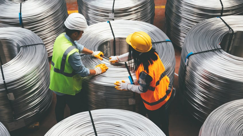 Aerial view of young engineer man and industrial worker woman checking production line and testing quality of steel pipe coils at warehouse section in cable factory.